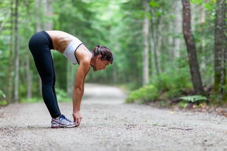 estiramientos: Mujer de mediana edad se extiende en el bosque en un camino de tierra antes de una carrera