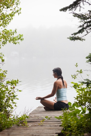 middle aged woman meditating on dock by a lake in the foggy morning, vertcal composition, Surry Maine photo