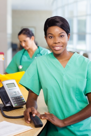 work station: Smiling African American nurse at hospital work station lit brightly with phone.  Second female medical professional in background Stock Photo
