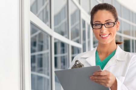 Smiling female caucasian doctor holding a clipboard in brightly lit exterior hospital environment in scrubs, white lab coat and wearing glasses. photo