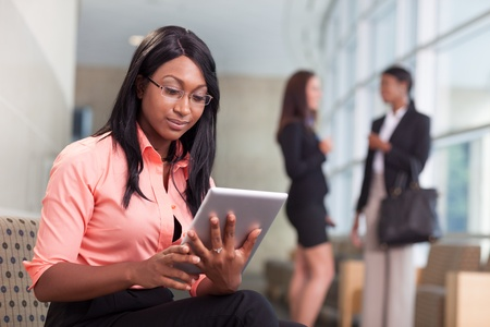 women talking: african-american business woman sitting in lobby, looking at tablet, two business women talking in background