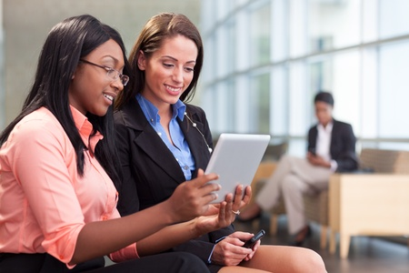Two businesswomen in foreground smile, looking at tablet together in lobby photo