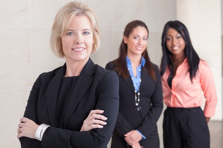 group of women: Three business women of varying ethnicities in suits, standing together, smiling and looking at camera, in office