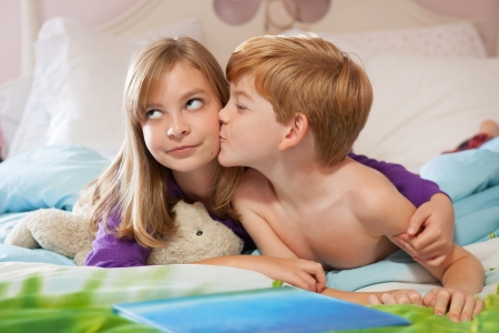 Blonde haired sister getting kissed on the cheek by red haired brother, lying on bed in pajamas  photo