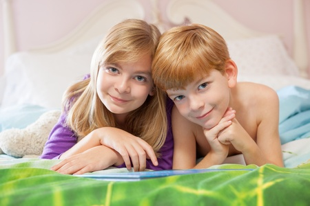 Blonde haired sister and red haired brother lying happily on bed in pajamas looking at camera. photo