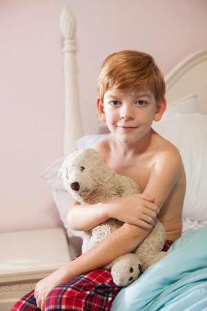 Young red-haired caucasian boy sitting on edge of bed in pajama bottoms, holding teddy bear.and smiling at camera. photo