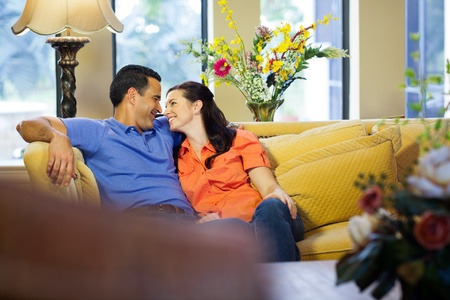 A hispanic man and a caucasian woman in jeans sit on a yellow couch cuddling and smiling at each other in their living room  photo