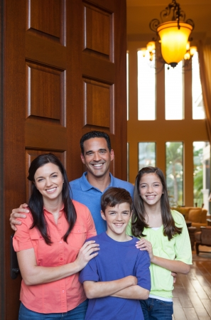 front house: Hispanic father, caucasian mother and mixed ethinicity son and daughter standing in entryway beside large wooden door of large home, living room with tall windows in background