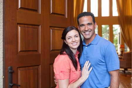 front house: Caucasian wife and hispanic husband standing in entryway of home with tall wooden door, and windows, high ceilings, smiling during day. Stock Photo