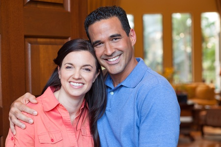 hispanic: Caucasian wife and hispanic husband standing in entryway of home with tall wooden door, and windows, high ceilings, smiling during day. Stock Photo