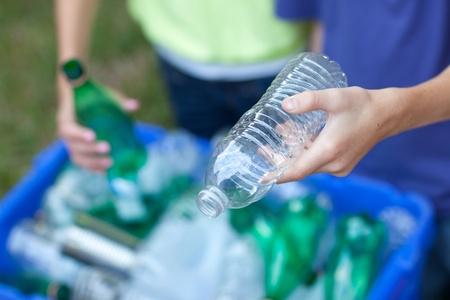 poubelle bleue: Caucase gar�on et une fille de mettre des bouteilles claires et vert et canettes m�talliques dans le bac de recyclage bleu � l'ext�rieur dans la cour Banque d'images