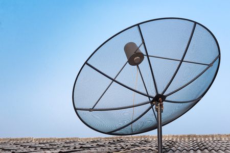 microwave antenna: Satellite dish on the roof with blue sky