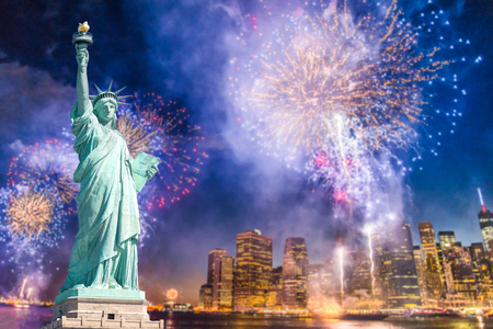 The Statue of Liberty with blurred background of cityscape with beautiful fireworks at night, Manhattan, New York City, USA