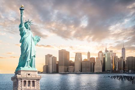 La estatua de la libertad con el fondo del Bajo Manhattan en la noche al atardecer, Monumentos históricos de la ciudad de Nueva York, EE.UU. Foto de archivo
