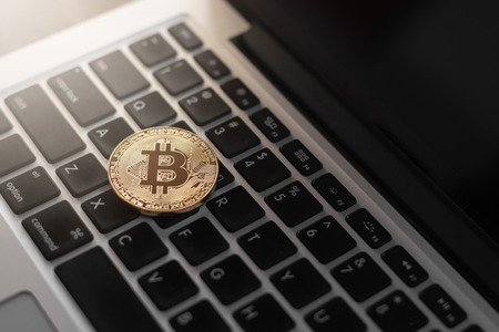Bitcoin physical coin symbol on laptop, future concept financial currency, crypto currency sign
