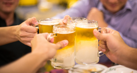 Soft focused group of people celebrate with cold beer, toasting the glass together in restaurant at night
