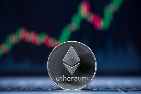 Ethereum physical coin symbol on laptop with uptrend price graph background, future concept financial currency, crypto currency sign