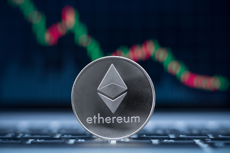 Ethereum physical coin symbol on laptop with downtrend price graph background, future concept financial currency, crypto currency sign Zdjęcie Seryjne