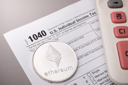 Ethereum physical coin symbol on tax form with calculator, smart contract crypto currency sign Zdjęcie Seryjne