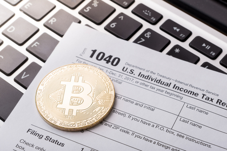 Bitcoin physical coin symbol on laptop with tax form, future concept financial currency, crypto currency sign
