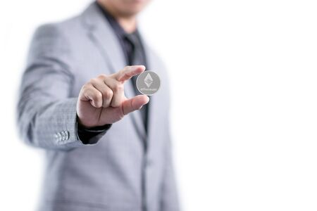 Businessman in gray suit is holding silver ethereum coin between fingers, smart contract crypto currency sign, isolated white background