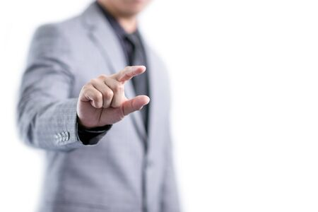Businessman in gray suit is showing something between fingers, isolated white background