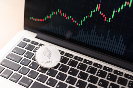 Ethereum physical coin symbol on laptop with uptrend price graph background, future concept smart contract financial currency, crypto currency sign