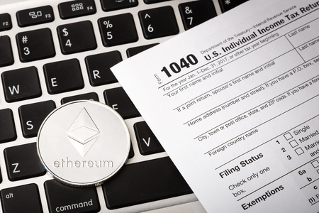Ethereum physical coin symbol on laptop with tax form, future concept smart contract technology, crypto currency sign