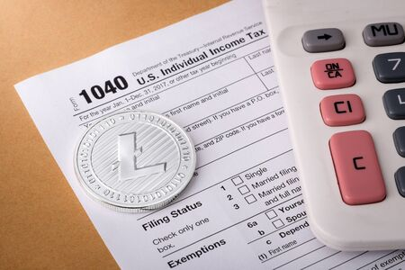 Litecoin physical silver coin symbol on 1040 tax form with calculator, concept of goods and services tax with crypto currency Zdjęcie Seryjne