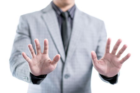 Businessman in gray suit is showing his two hands to stop something, isolated white background with clipping path