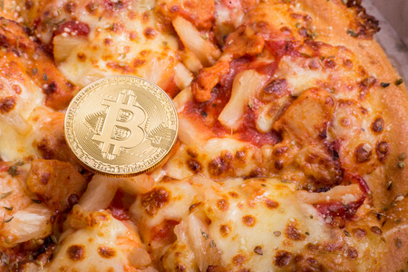 Pizza and golden physical bitcoin, concept of buying pizza with bitcoin, bitcoin pizza day anniversary