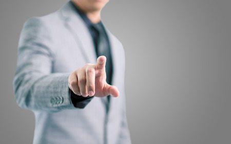 Businessman in gray suit is pointing his finger to touch the screen concept with gray background