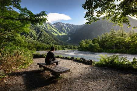 Man sitting on bench alone in Kamikochi national park summer season, Matsumoto, Japan