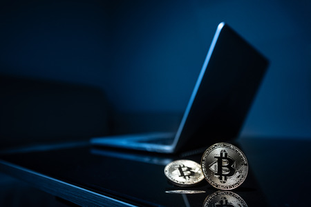 Bitcoin physical coin symbol with laptop background in the dark room