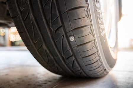 Close-up nail or screw stick on the car tire, the most problem of flat tire Zdjęcie Seryjne - 141215026