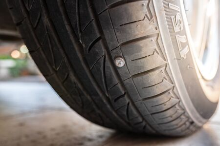 Close-up nail or screw stick on the car tire, the most problem of flat tire 免版税图像