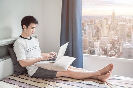 Man works from home using laptop in bedroom with aerial city view through the window to avoid coronavirus or covid-19 pandemic