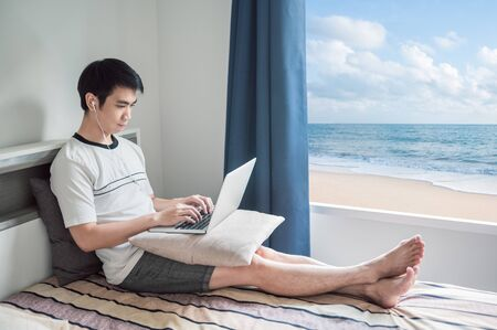 Man works from home using laptop in bedroom with beach view through the window 免版税图像