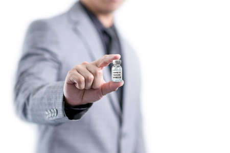 Man in grey suit showing a  vaccine in his hand with white copy space 免版税图像