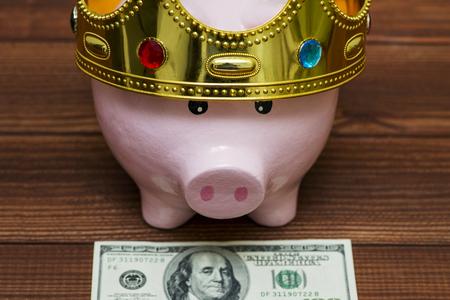 A piggy bank with a corona put on a hundred-dollar bill