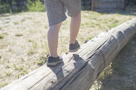 Little boy walking on a log in the park. child on the balance beam Banque d'images