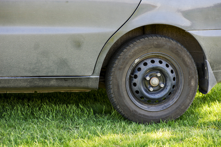 The dirty car, the car costs on a green grass in the field, the fender close up splodgy with dirt