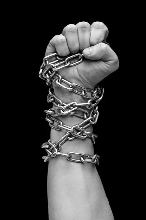 Fist of man in chains. Black and white Stock Photo