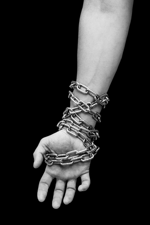 Hand of slave with chains. Hand tied chain Stock Photo
