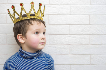 Little child with a crown on his head against a white brick wall