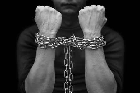 Male hands with chain wrapped around them, prisoner concept. Hostage concept