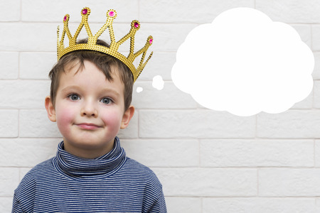 Small child in a crown with a think bubble Stock fotó