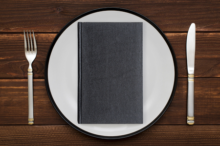 Book on plate with knife and fork. Concept image of a book as main course