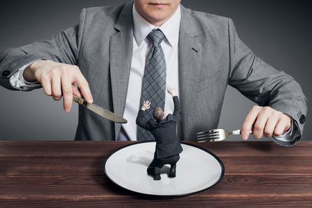 Businessman holding fork with knife and ready to eat small scared businessman on the plate. Hungry businessman ready to eating a competitor 写真素材