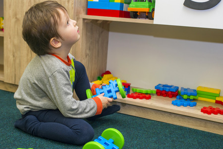 Little child plays with toys in kindergarten Stock Photo